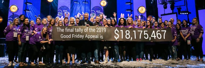 "Group of volunteers, our Director Anne Randall and channel 7 news reader Peter Mitchell holding a sign that reads ""The final tally of the 2019 Good Friday Appeal is $18,175,467""."