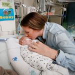 Mum Kimberley kissing her baby Sonny on the head in his hospital crib