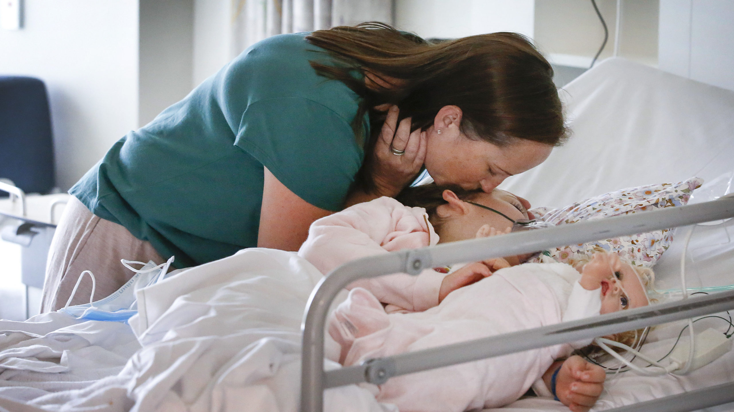 Mum Sara kisses her daughter Piper who is lying in her hospital bed