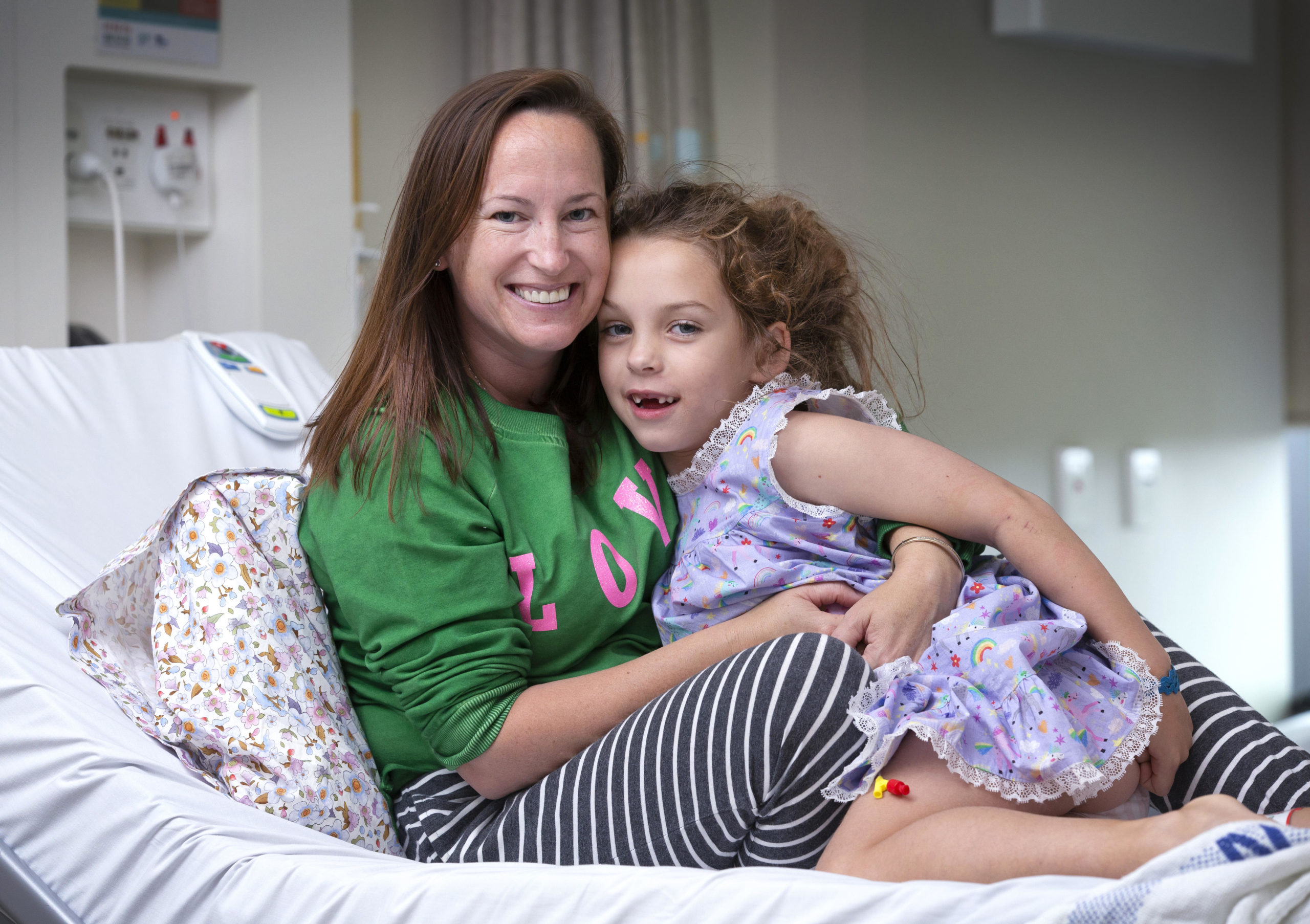 Piper sitting with her mum Sara on her hospital bed